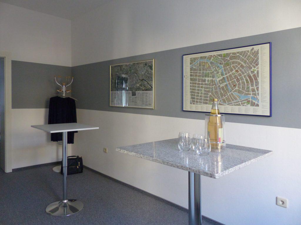 Schulungsraum nach Umgestaltung mit weißer Wand und grauem Farbstreifen über Stehtische