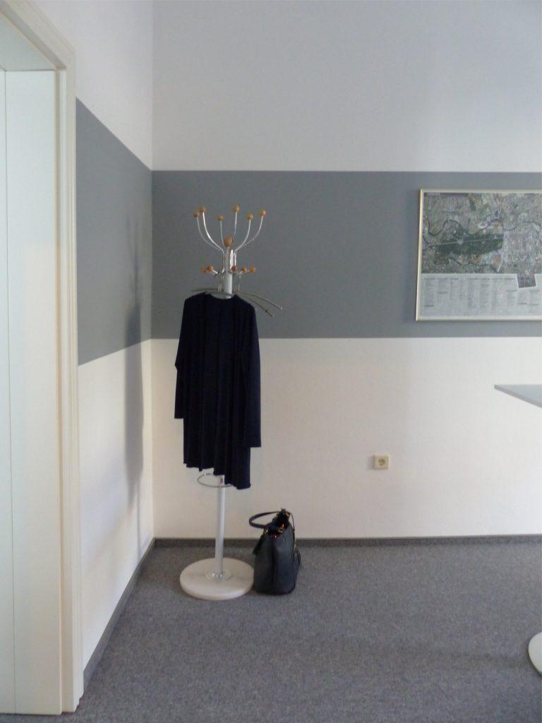 Schulungsraum nach Umgestaltung mit weißer Wand und grauem Farbstreifen vor Garderobenständer und Wandbild