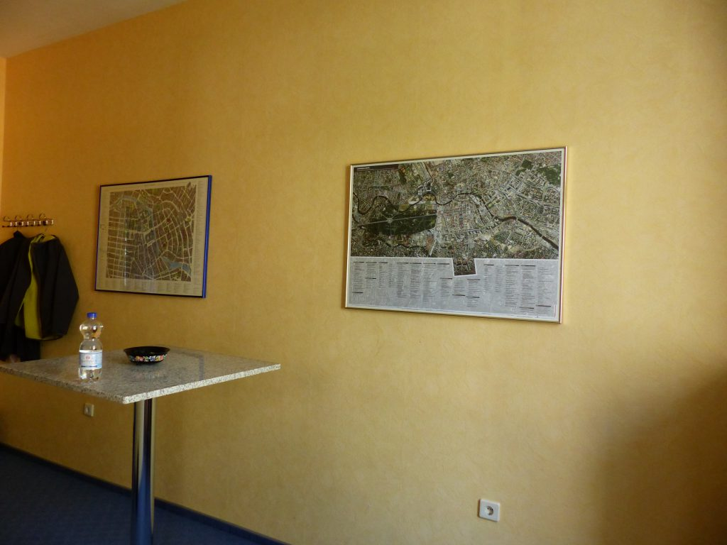 Schulungsraum vor Umgestaltung mit gelber Wand vor Stehtisch und Wandbildern