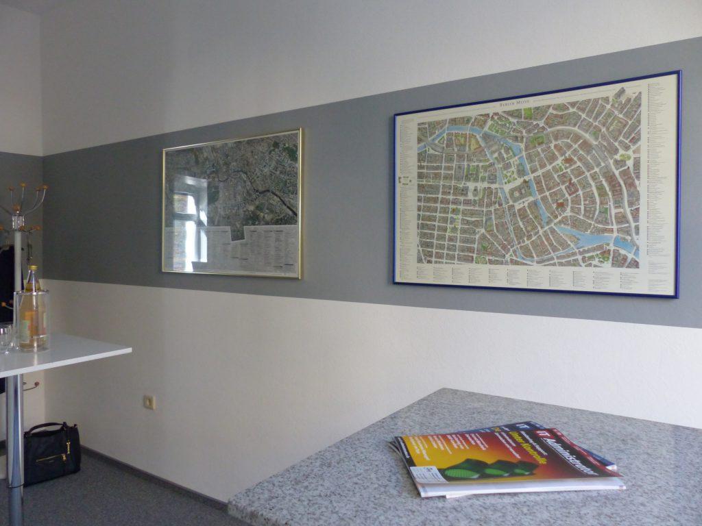 Schulungsraum nach Umgestaltung mit weißer Wand und grauem Farbstreifen als Rahmen für Wandbilder