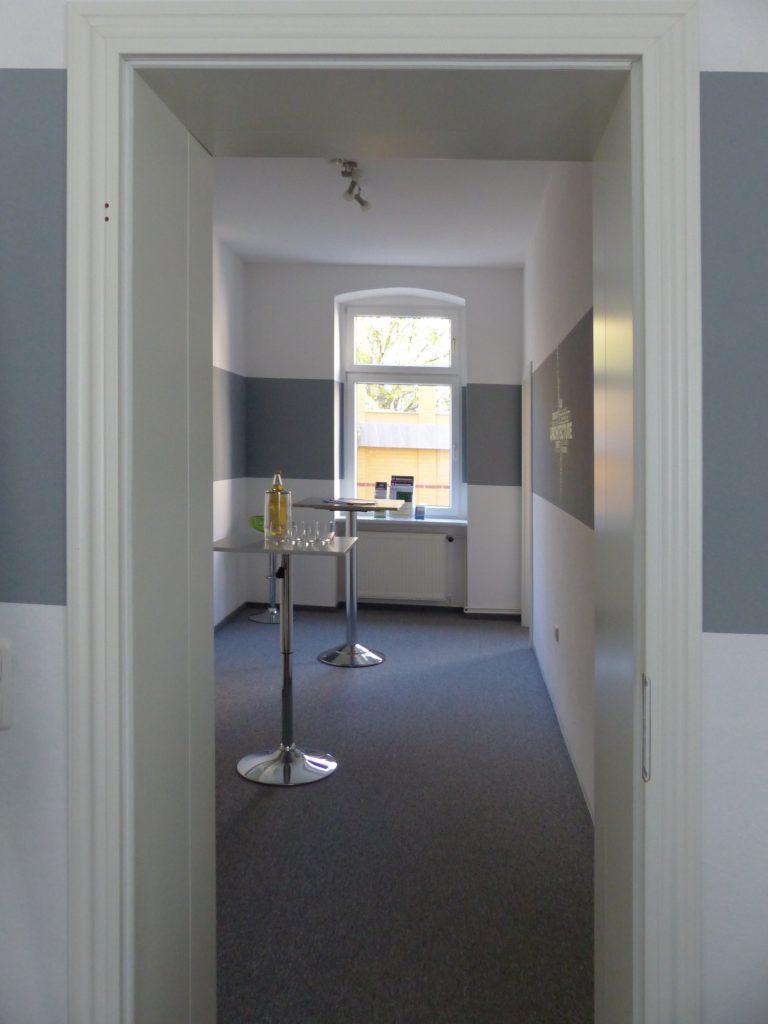 Schulungsraum nach Umgestaltung mit Fenster in weißer Wand und grauerm Farbstreifen und Stehtischen auf grauem Teppich