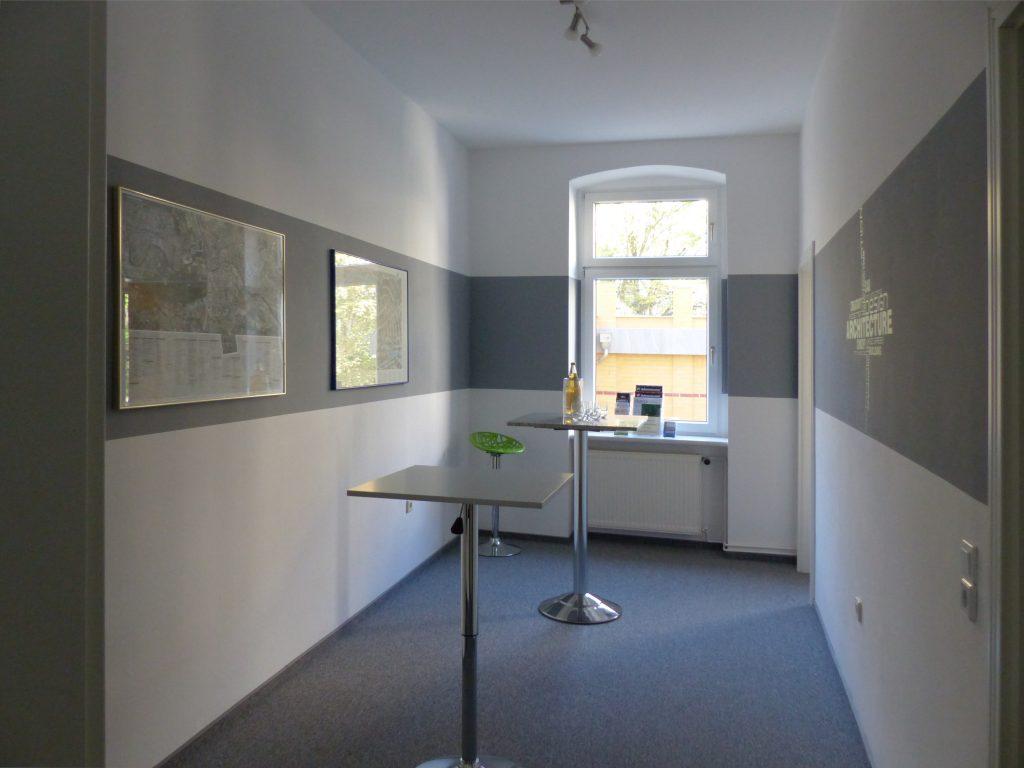 Schulungsraum nach Umgestaltung mit Fenster und Bildern in weißer Wand und grauerm Farbstreifen und Stehtischen auf grauem Teppich