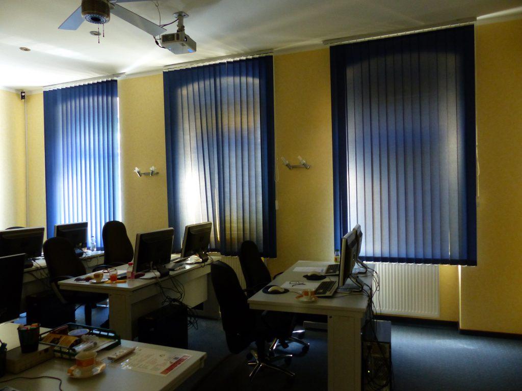 Schulungsraum vor Umgestaltung mit gelber Wand und blauen Vorhängen