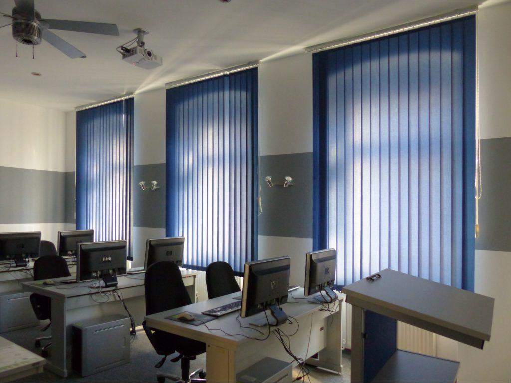 Schulungsraum nach Umgestaltung mit weißer Wand und grauem Farbstreifen und blauen Vorhängen