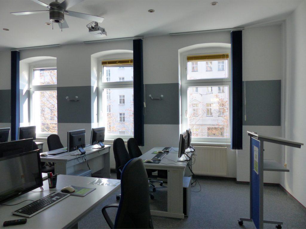 Schulungsraum nach Umgestaltung mit weißer Wand und Wandleuchten vor grauem Farbstreifen