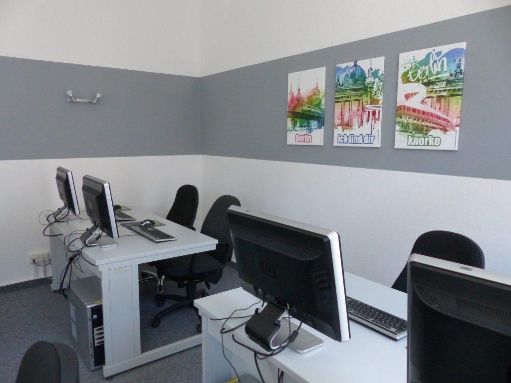 Schulungsraum nach Umgestaltung Rückseite mit weißer Wand und grauem Farbstreifen als Rahmen für drei Wandbilder