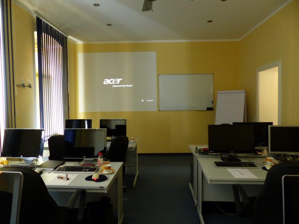 Schulungsraum vor Umgestaltung Vorderseite mit weißer Präsentationsfläche vor gelber Wand