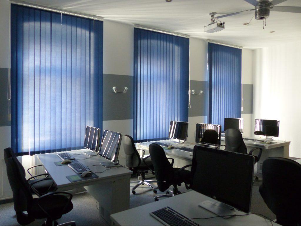 Schulungsraum nach Umgestaltung Schulungsplätze vor weißer Wand mit grauem Farbstreifen und geschlossenen blauen Vorhängen