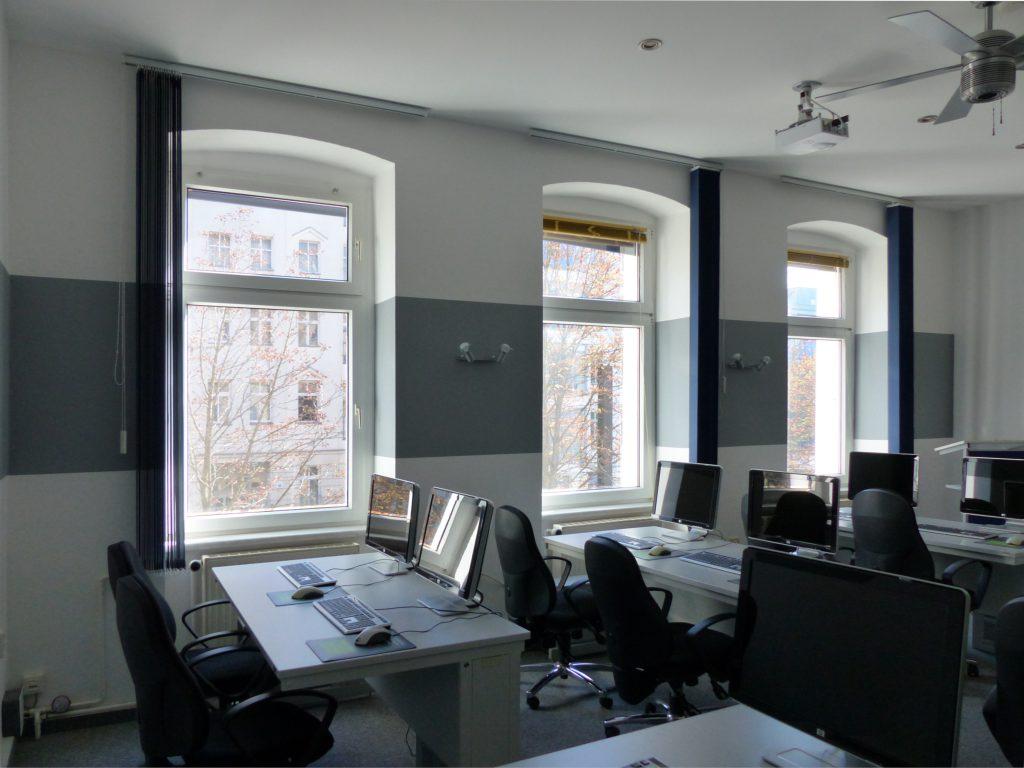 Schulungsraum nach Umgestaltung Schulungsplätze vor weißer Wand mit grauem Farbstreifen und geöffneten blauen Vorhängen