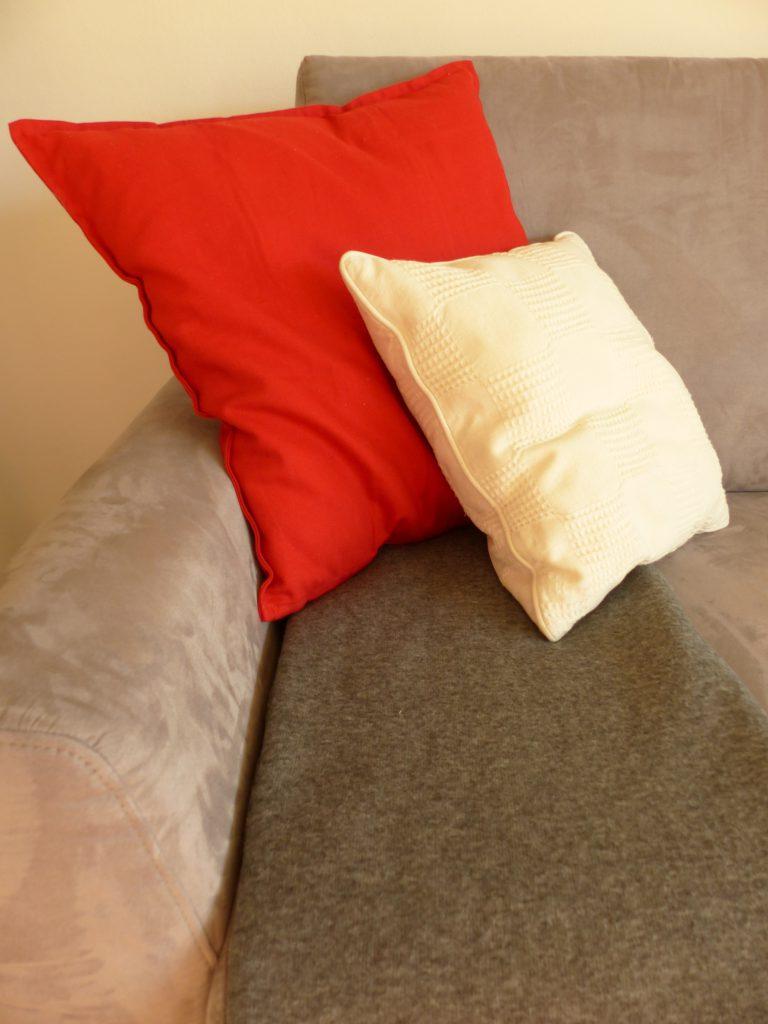 altes Klavier nach Umgestaltung mit rotem und weissem Kissen auf grauem Sofa