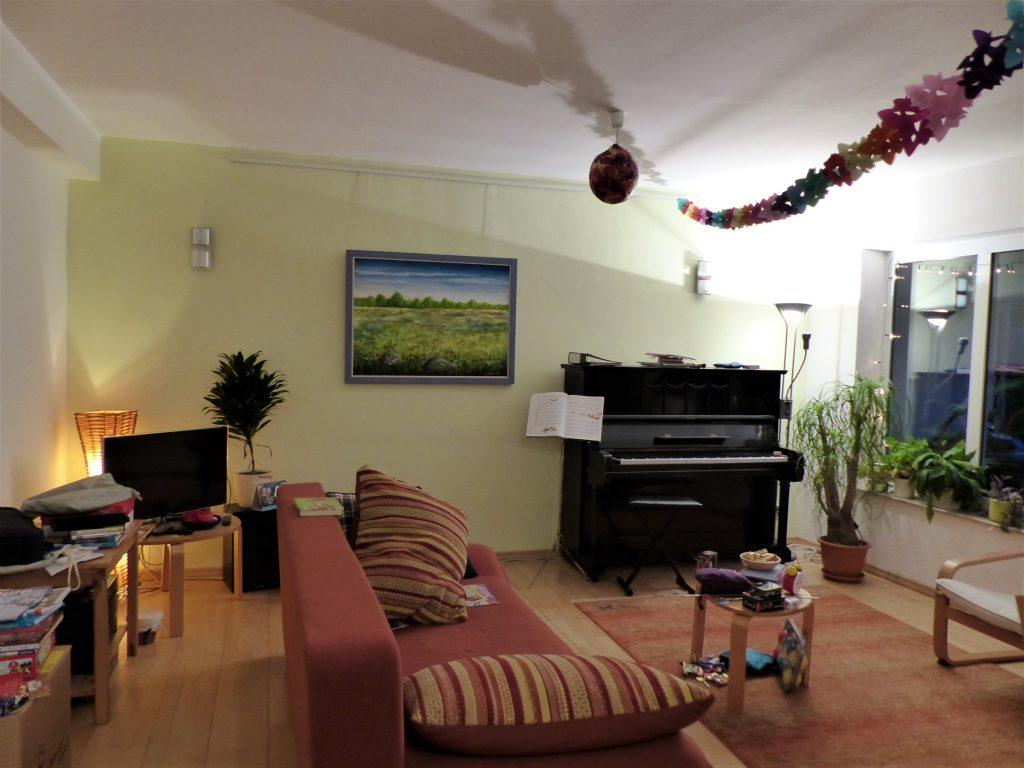 altes Klavier vor Umgestaltung mit altem Sofa und Wandbild vor gelber Wand