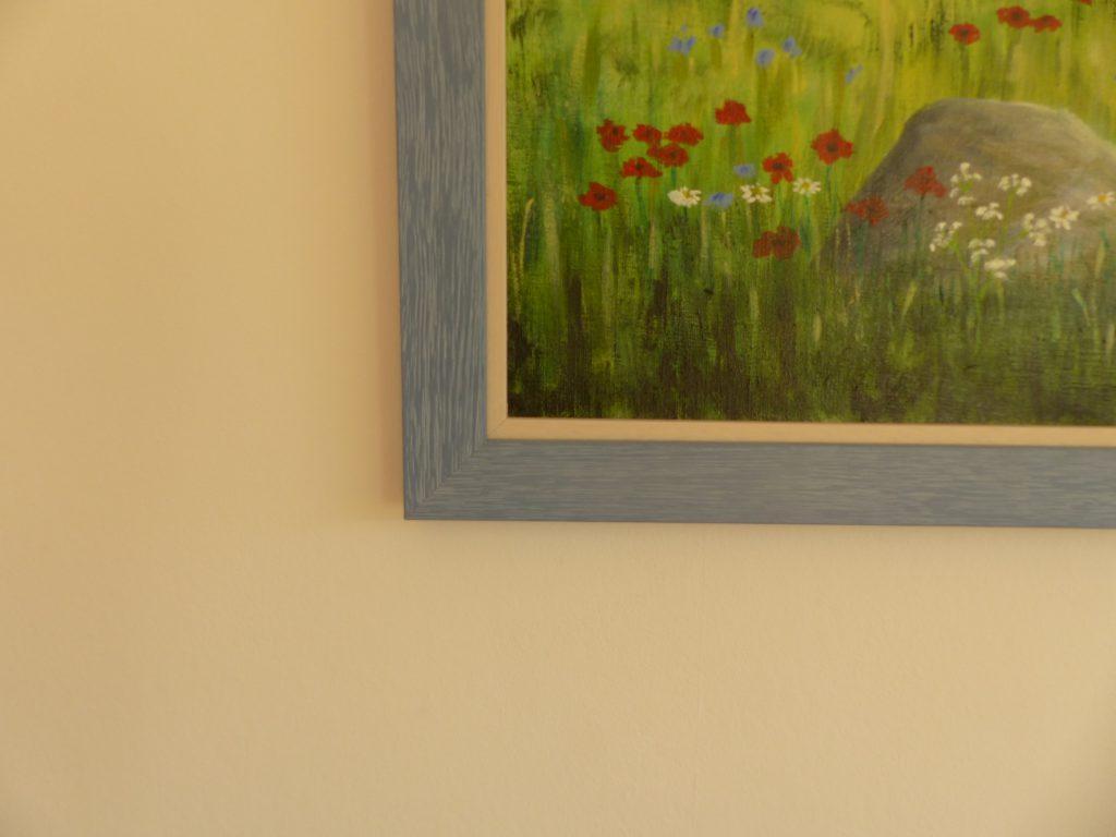 altes Klavier nach Umgestaltung mit Wandbilddetail grauer Rahmen und rote Blumen