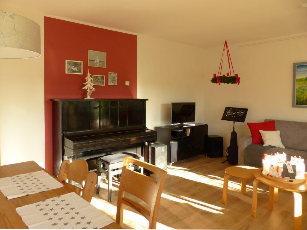 altes Klavier nach Umgestaltung mit Essplatz, schwarzem Fernseh-Sideboard, Notenständer und grauem Sofa
