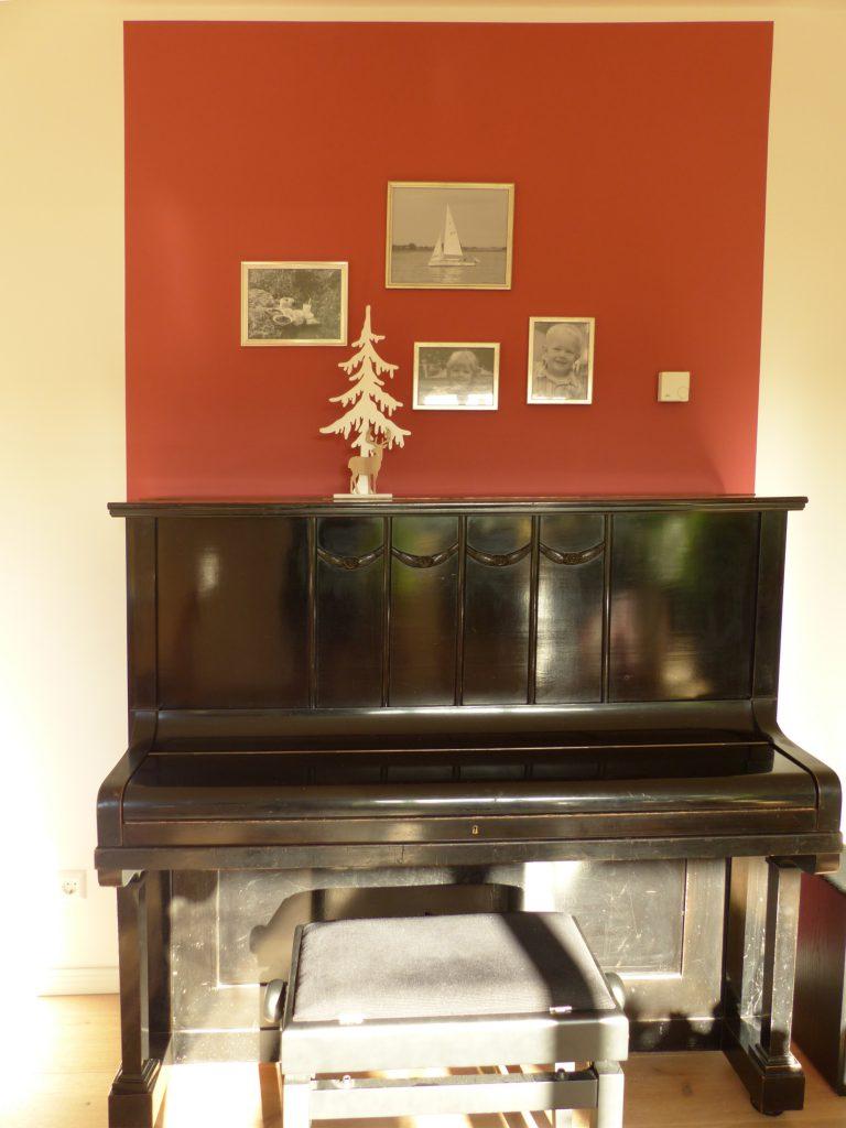 altes Klavier nach Umgestaltung mit Klavierhocker und weissen Bilderrahmen vor rotem Farbspiegel an der Wand