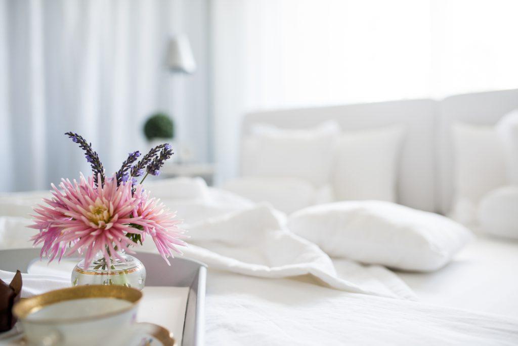 weisses Schlafzimmer Fertig mit Tasse und Blumen in Vase